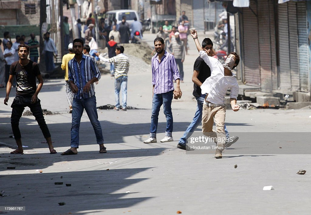 Protesters throw stones at paramilitary soldiers during a protest against killing of 4 people in BSF firing on July 18, 2013 in Srinagar, India. Four people were killed today when security personnel opened fire at a mob that had gathered at a BSF camp in Ramban district protesting against alleged manhandling of an Imam of the area by the force. Curfew would be imposed in Srinagar and all other major towns in the Kashmir Valley from Friday morning as a precautionary measure.