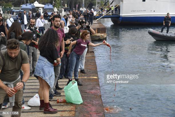 Protesters throw tomato sauce in the port of Italian island Ischia to symbolize migrants who died at sea trying to cross the Mediterranean on October...