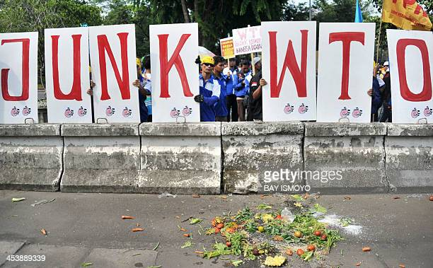 Protesters throw vegetables during ananti WTO rally in front of the US embassy in Jakarta on December 6 2013 World commerce ministers engaged in...
