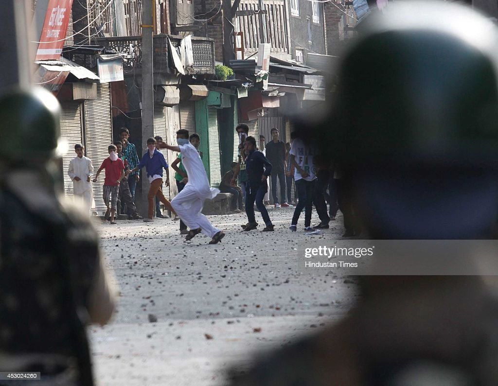 Protesters throwing stones on policemen during a protest called by Syed Ali Shah Geelani, separatist leader, following separatists' call for post-prayers protests against the Kaunsar Nag Yatra, which the government halted from the Aharbal route in the Kashmir valley, on August 1, 2014 in Srinagar, India. Geelani accused chief minister Omer Abdullah of 'being only concerned with his chair and not caring about the negative effects of this decision in haste'. Clashes erupted in many parts of Kashmir after the Friday congregational prayers over the government's decision to allow a pilgrimage to Kausarnag- a glacial lake in southern parts of the valley.