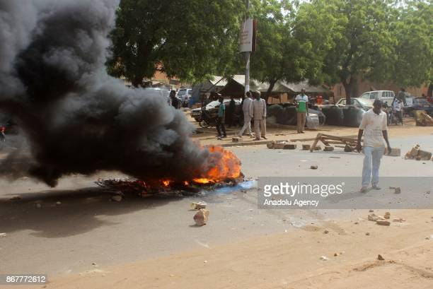 Protesters try to block the road with fire as they stage a protest against government's budget law of 2018 in Niamey Niger on October 29 2017