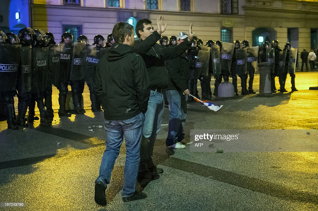 Protesters try to calm other violent protesters during a protest against the Slovenian government in Ljubljana, on November 30, 2012. At least 10 officers were injured as a group of protesters threw stones and bottles at them towards the end of what had been a largely peaceful protest against the centre-right government, police spokesman Vinko Stojnsek told AFP. AFP PHOTO