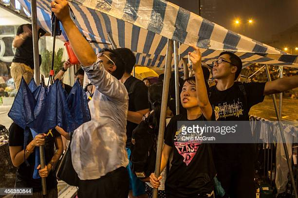 Protesters try to hold up a makeshift tent during a heavy rain storm outside the Hong Kong Government Complex on September 30 2014 in Hong Kong Hong...