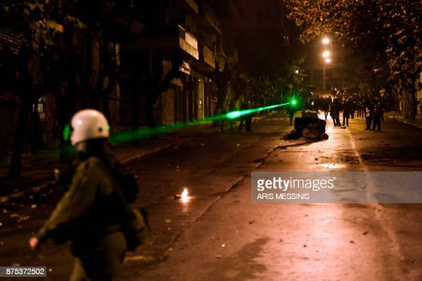 Protesters use a laser to light up antiriot policemen in downtown Athens on November 17 during clashes following a rally commemorating the 1973...