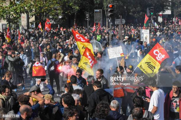 Protesters use smoke lightning while shouting slogans as they take part in a protest during the nationwide strike called by various French unions...
