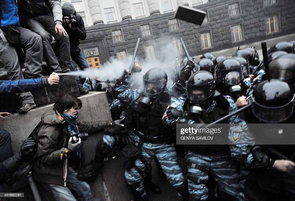 Protesters use tear gas and throw stones during clashes with riot police in front of the Cabinet of Ministers of Ukraine during a rally in Kiev on November 24, 2013. Thousands of pro-Europe protesters in Ukraine attempted to storm the government building in the capital of Kiev Sunday, clashing with police who fired tear gas to keep them back. Protesters tried to break through police ranks surrounding the building, with some throwing stones and hitting officers with the signs they were carrying, as police fought back with batons, an AFP correspondent reported.
