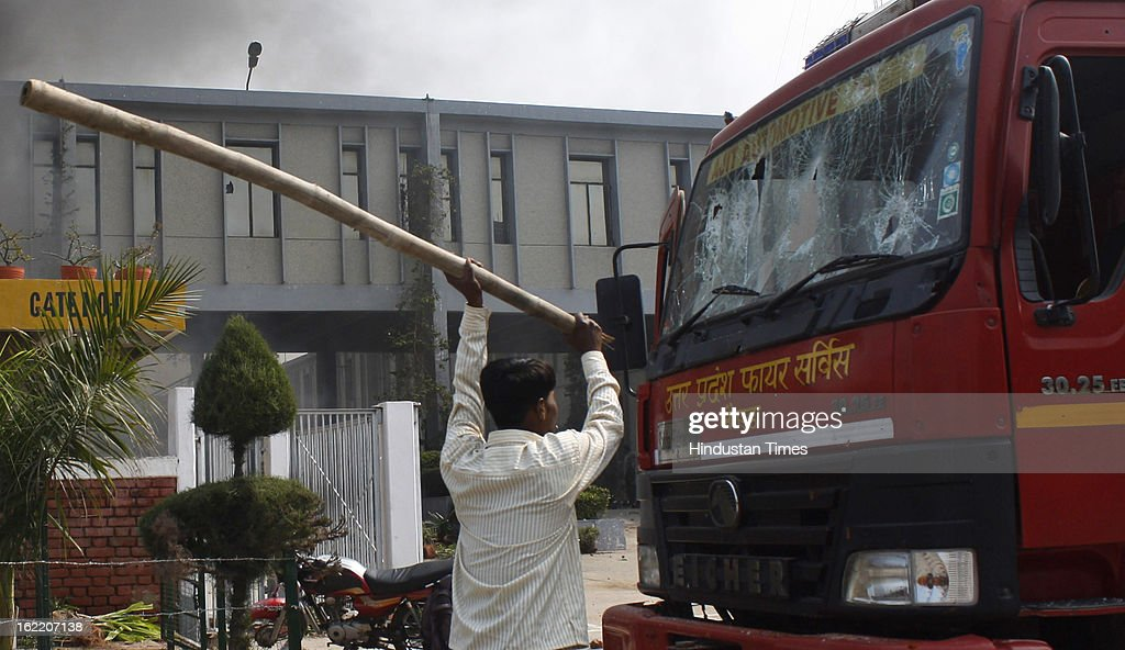 Protesters vandalizing the vehicle during the two-day nationwide strike called by various trade unions to protest against Government's economics and labour policies, on February 20, 2013 in Noida, India. Protest turned violent at Phase II in Noida as protesters pelted stones at factories and set seven to eight vehicles on fire.
