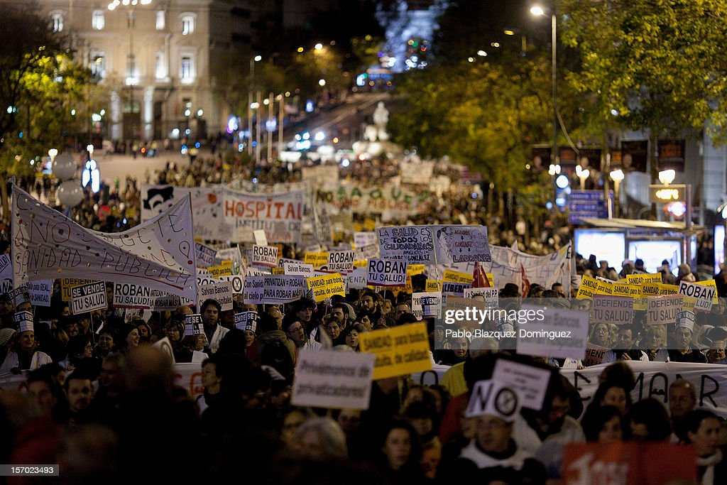 Protesters walk along Alcala Street amid other health workers during a demonstration held on the second day of a two-day general strike on November 27, 2012 in Madrid, Spain. For the first time all trade unions called for a 48-hour general health workers strike in the Madrid region after the regional government announced severe cuts and privatization of medical centers.