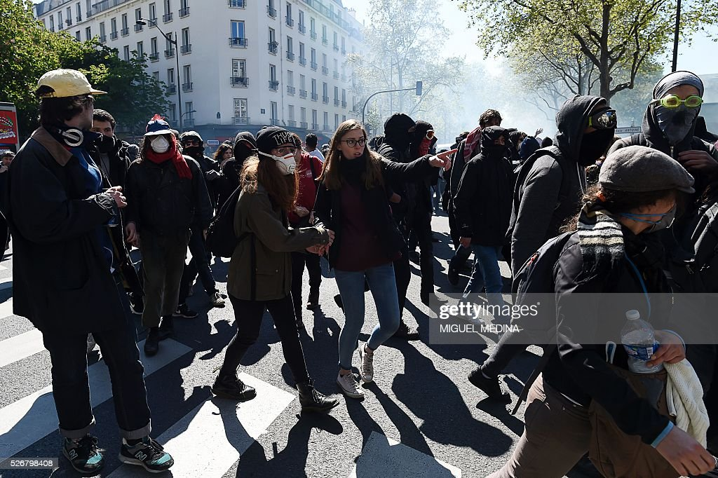 Protesters walk as clashes break out with police at a traditional May Day demonstration on May 1, 2016, in Paris.
