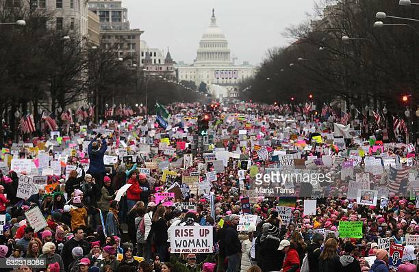 Protesters walk during the WomenÕs March on Washington with the US Capitol in the background on January 21 2017 in Washington DC Large crowds are...