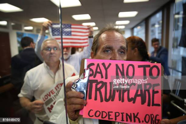 Protesters walk out of the office of Sen Dean Heller in the Hart Senate Office Building on July 17 2017 in Washington DC The protesters were asking...