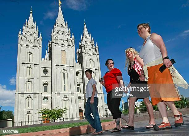 Protesters walk past the Mormon Temple on the Main Street Plaza holding hands July 12 2009 in Salt Lake City Utah The protesters defied church...