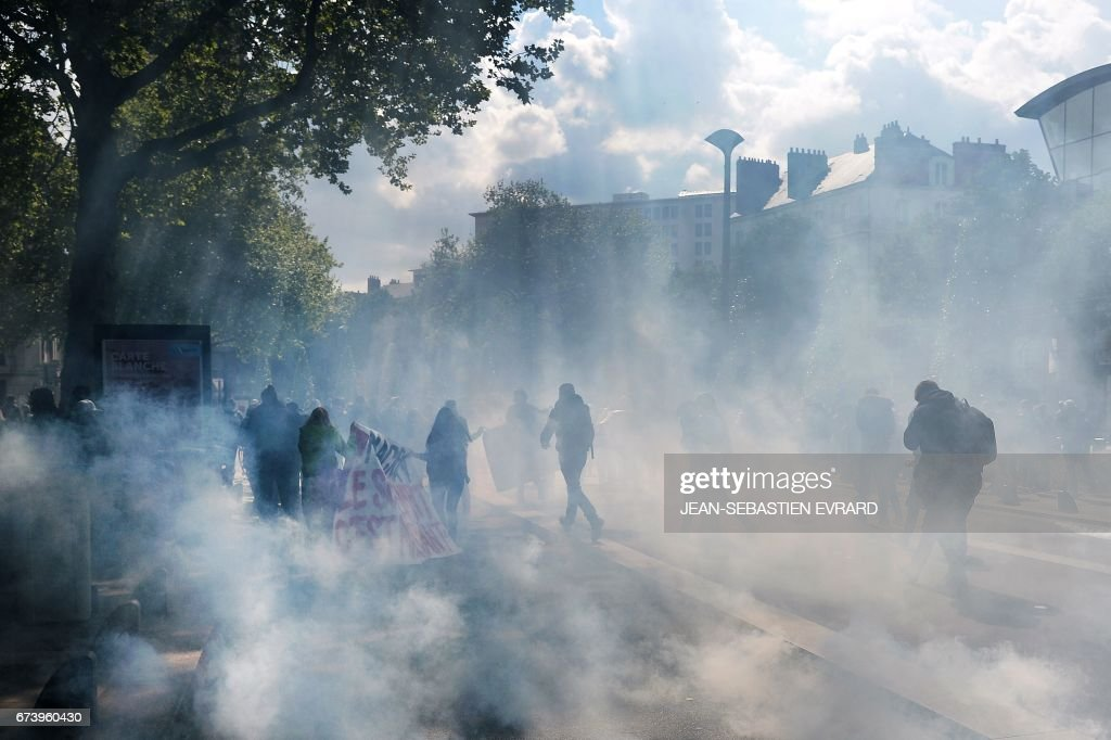 Protesters walk through a cloud of tear gas during a demonstration against the results of the first round of the French presidential election in Nantes, western France, on April 27, 2017. Youths gathered to protest against far-right leader Marine Le Pen and former banker Emmanuel Macron, who both qualified on April 23 for the May 7 run-off in France's two-stage presidential election.