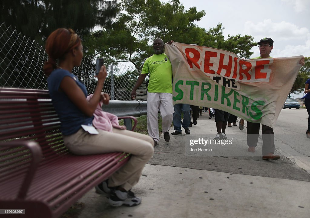 Protesters walk together to a Walmart store as they target the company which they say needs to improve working conditions and rehire workers they say were fired for engaging in labor activities on September 5, 2013 in Miami Gardens, Florida. The protesters joined with others across the nation during a day of action against the company.