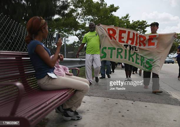 Protesters walk together to a Walmart store as they target the company which they say needs to improve working conditions and rehire workers they say...