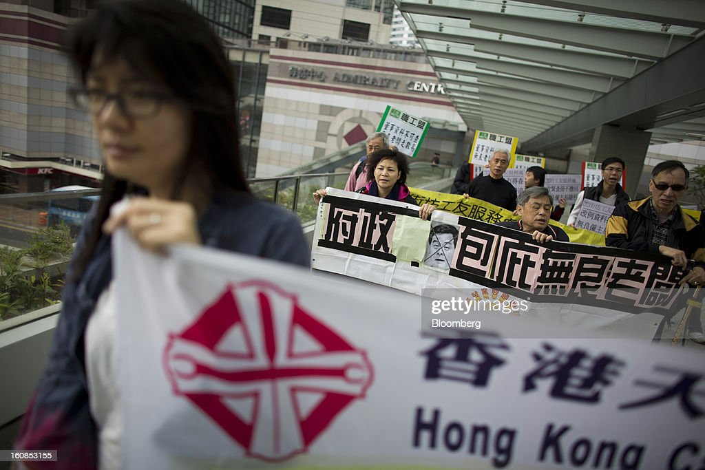 "Protesters walk with banners during a march organized by labor unions in Hong Kong, China, on Thursday, Feb. 7, 2013. The Financial Services and the Treasury Bureau and the city's Companies Registry put forward a proposal to ""enhance protection of the privacy of personal information,"" in November as part of a consultation paper on a new companies ordinance. The proposed amendments would make tracing the personal details of company directors in the city more difficult. Photographer: Lam Yik Fei/Bloomberg via Getty Images"