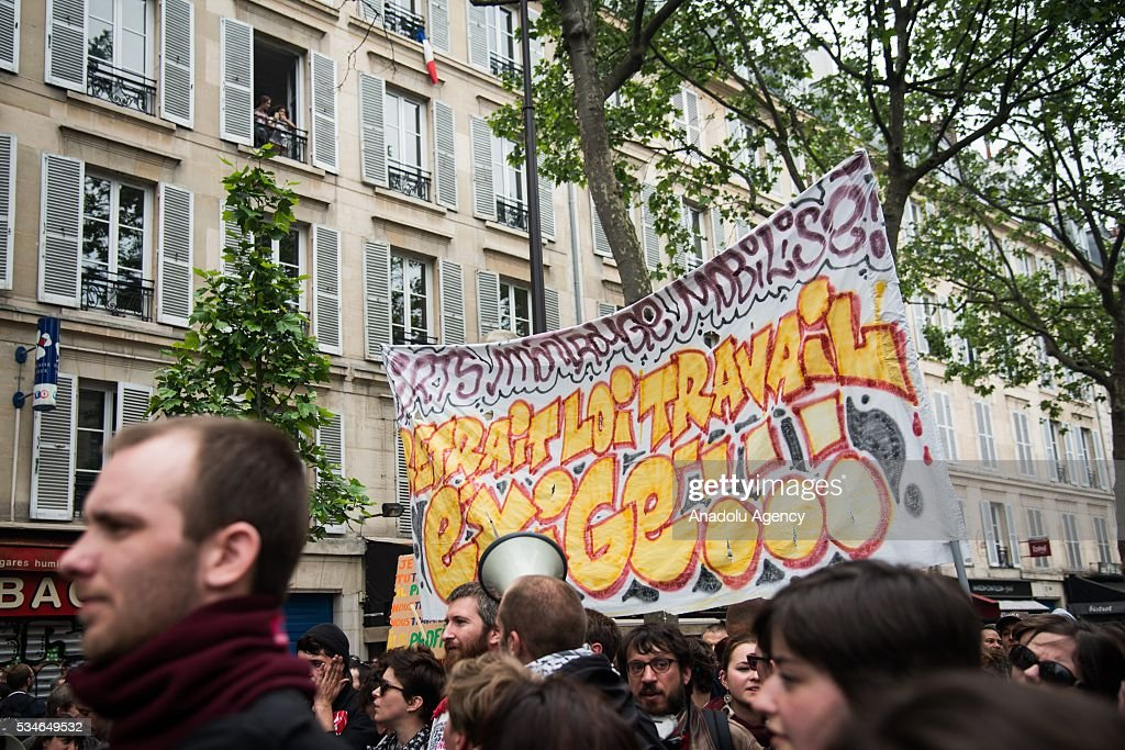 Protesters walk with banners during the protest against French government's labor law reform in Paris, France on May 26, 2016
