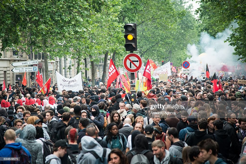 Protesters walk with banners during the protest against French government's labor law reform in Paris, France on May 26, 2016.