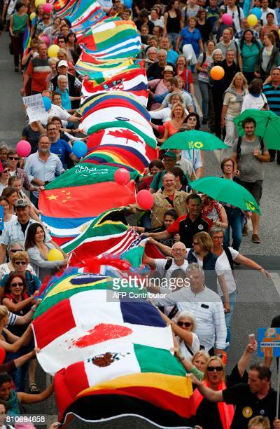 Protesters walk with hundreds of flags of the countries of the world during the 'Hamburg zeigt Haltung' demonstration on July 8 2017 in Hamburg...