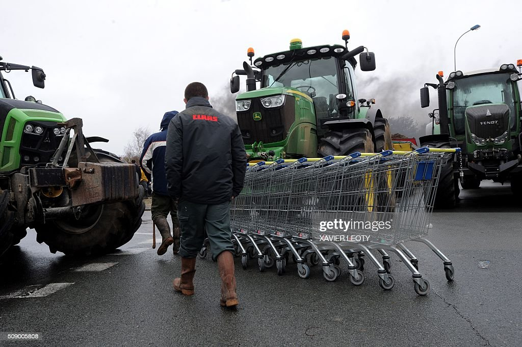 Protesters walks past tractors and shopping trolleys as they block a road near Saintes, western France, on February 8, 2016, during a demonstration by farmers against the purchase price of their products by supermarkets. Over 100 tractors were used by mostly pig and dairy farmers to block strategic points giving access to the city, disrupting traffic and closing an interchange of the A10 motorway. / AFP / XAVIER LEOTY