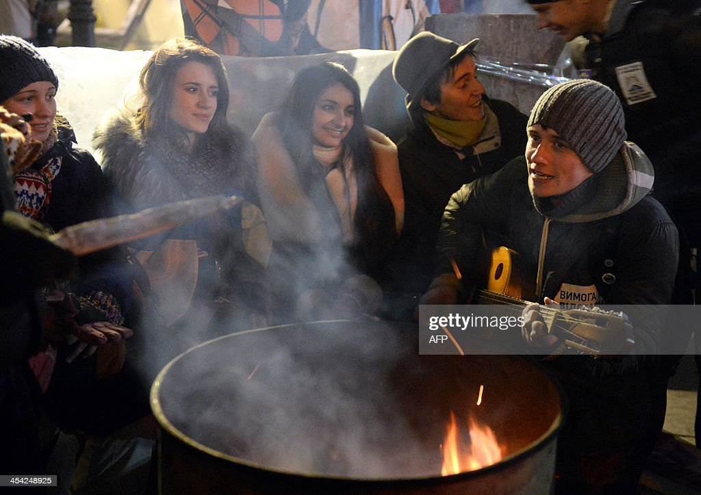 Protesters warm near a fire barrel during an opposition rally on Independence Square in Kiev on December 7, 2013. Some 200,000 pro-EU protesters massed in Kiev on Sunday for a new demonstration aimed at wringing concessions from President Viktor Yanukovych in a bitter confrontation over a rejected EU deal.