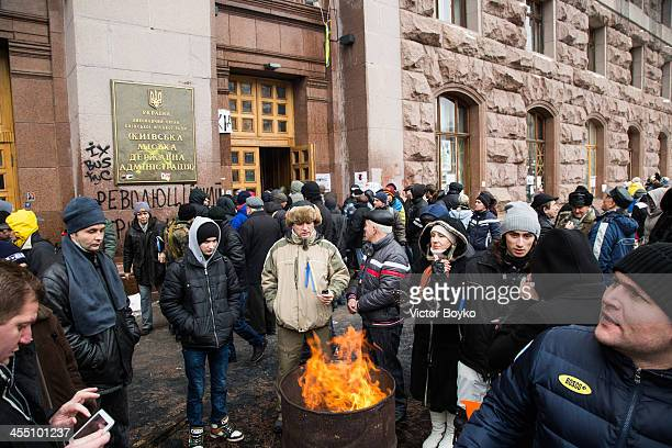 Protesters warm themselves near a fire outside the City Hall entrance after the riot police were forced out from blocking the front door as...