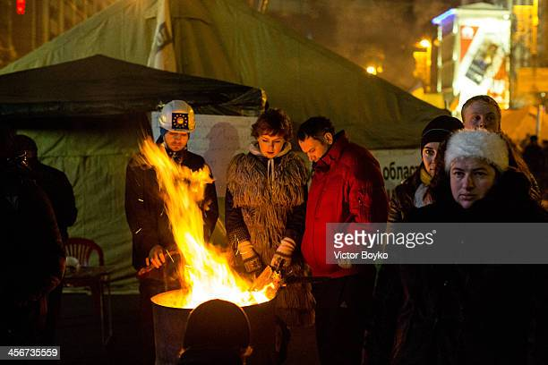 Protesters warm themselves while standing in Maidan Square on December 14 2013 in Kiev Ukraine Antigovernment protests began three weeks ago when...