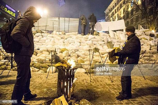 Protesters warming up themselves while other protesters installing metal sheet barriers and barbed wire on a new reinforced barricade on Maidan...