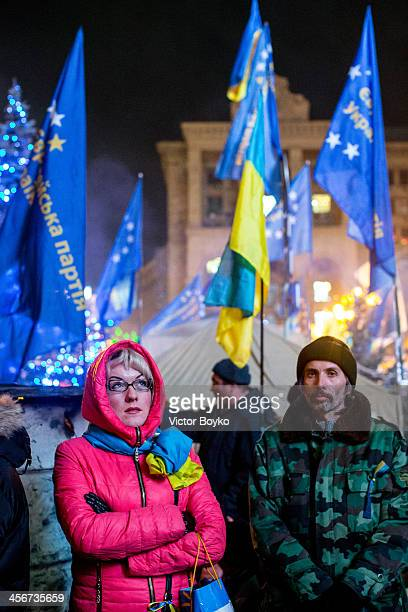Protesters watch a TV screen on Maidan Square as protests continue on December 14 2013 in Kiev Ukraine Antigovernment protests began three weeks ago...