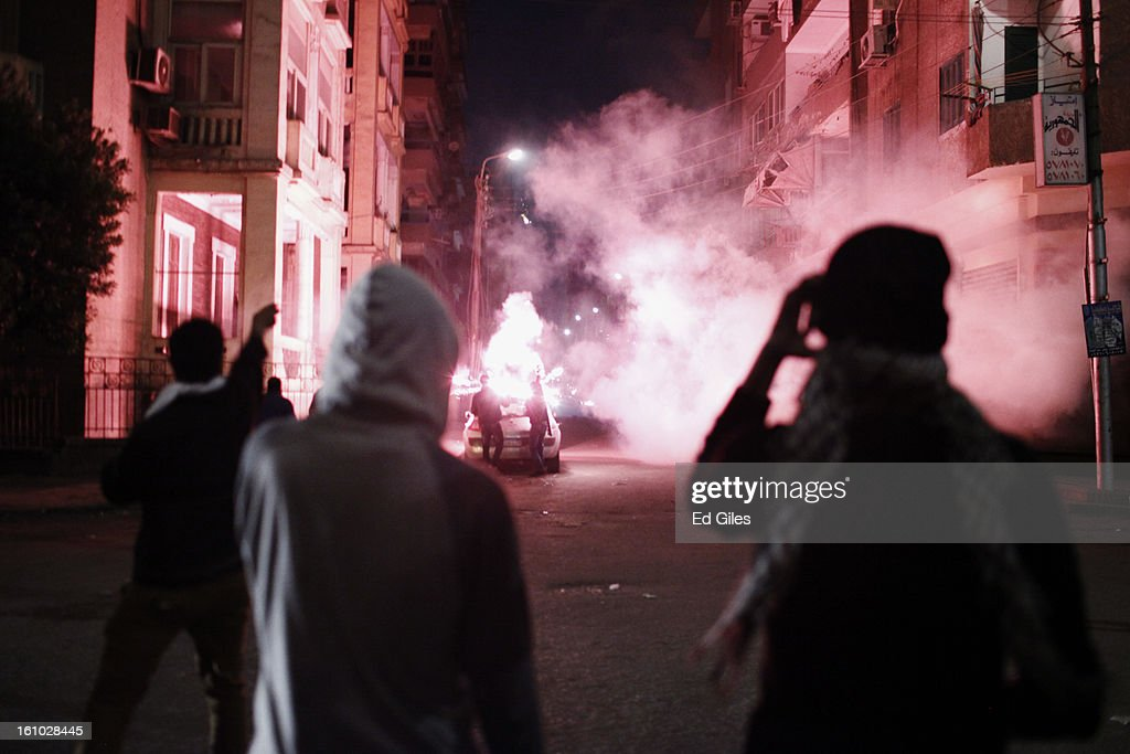 Protesters watch as other demonstrators fire fireworks toward nearby Egyptian riot police during violent protests at the Presidential Palace in Heliopolis on February 8, 2013, in Cairo, Egypt. Protests continued across Egypt against President Morsi and the Muslim Brotherhood two weeks after the second anniversary of the Egyptian Revolution that overthrew former President Hosni Mubarak on January 25, 2011.(Photo by Ed Giles/Getty Images).