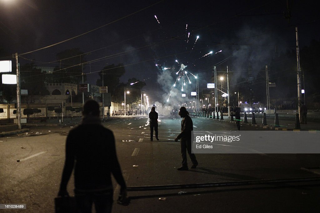Protesters watch as other demonstrators set off fireworks at nearby Egyptian riot police during violent protests near the Presidential Palace in Heliopolis on February 8, 2013, in Cairo, Egypt. Protests continued across Egypt against President Morsi and the Muslim Brotherhood two weeks after the second anniversary of the Egyptian Revolution that overthrew former President Hosni Mubarak on January 25, 2011.(Photo by Ed Giles/Getty Images).