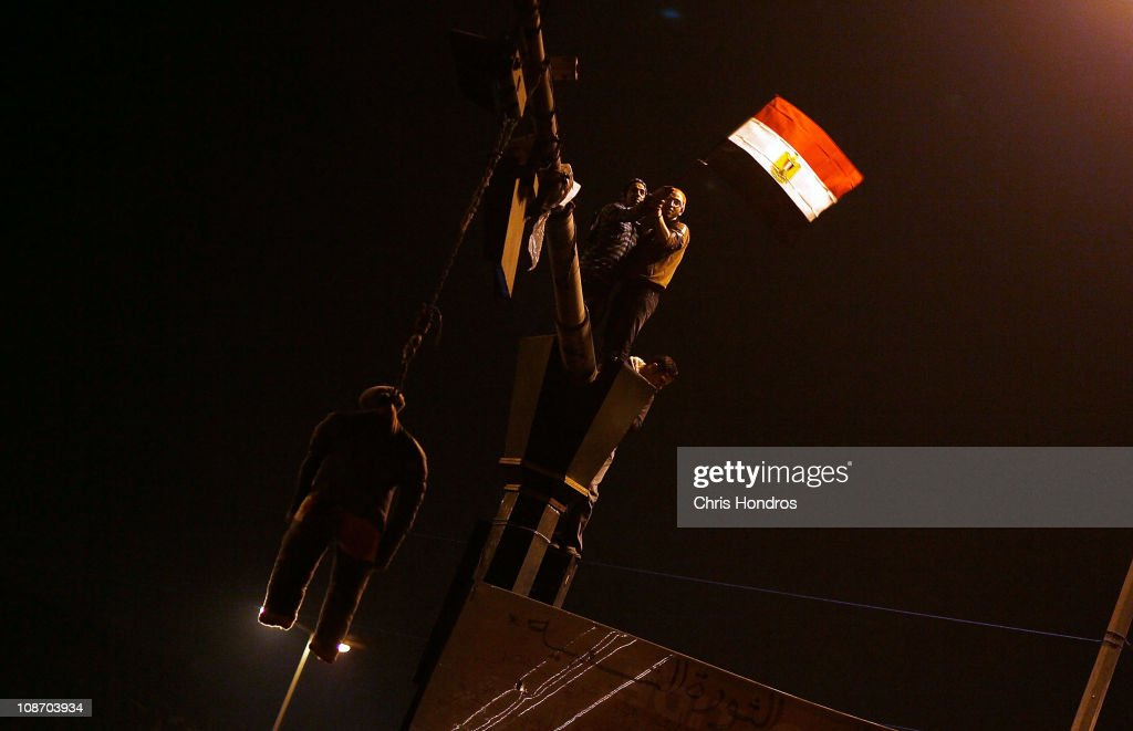 Protesters wave a flag from a light pole near an effigy of Egyptian president Hosni Mubarak after he gave a speech on his political future in Tahrir Square February 1, 2011 in Cairo, Egypt. In a pre-recorded televised address to the country, President Mubarak announced that he would not run for another term in office, but whether protesting Egyptians would agree with him about staying in office until elections later this year is uncertain.