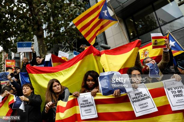Protesters wave flags and banners during a gathering of pro and antiSpanish unity demonstrators following a news conference with Catalonia's...