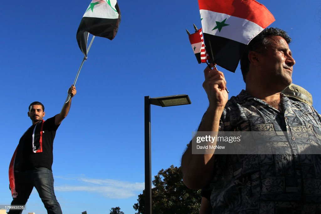 Protesters wave flags at a rally to urge Congress to vote against a limited military strike against the Syrian military in response to allegations that President Bashar Hafez al-Assad has used sarin gas to kill civilians on September 7, 2013 in Los Angeles, California. The Obama administration claims to have clear evidence that the Syrian military broke international law by killing nearly 1,500 Syrian civilians, including at least 426 children, in a chemical weapons attack on August 21, and is seeking the support of Congress for a missile strikes to prevent future chemical weapons attacks by the regime and other nations.