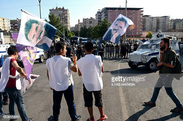 Protesters wave flags of jailed Kurdish leader Abdullah Ocalan opposite Turkish riot police in Diyarbakir on August 1 2015 during a demostration...