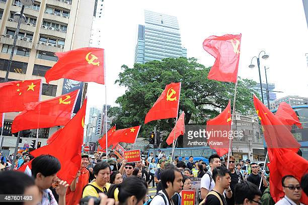 Protesters wave flags of People's Republic of China and Communist Party of China as they march on a street during a rally on May 1 2014 in Tsim Sha...