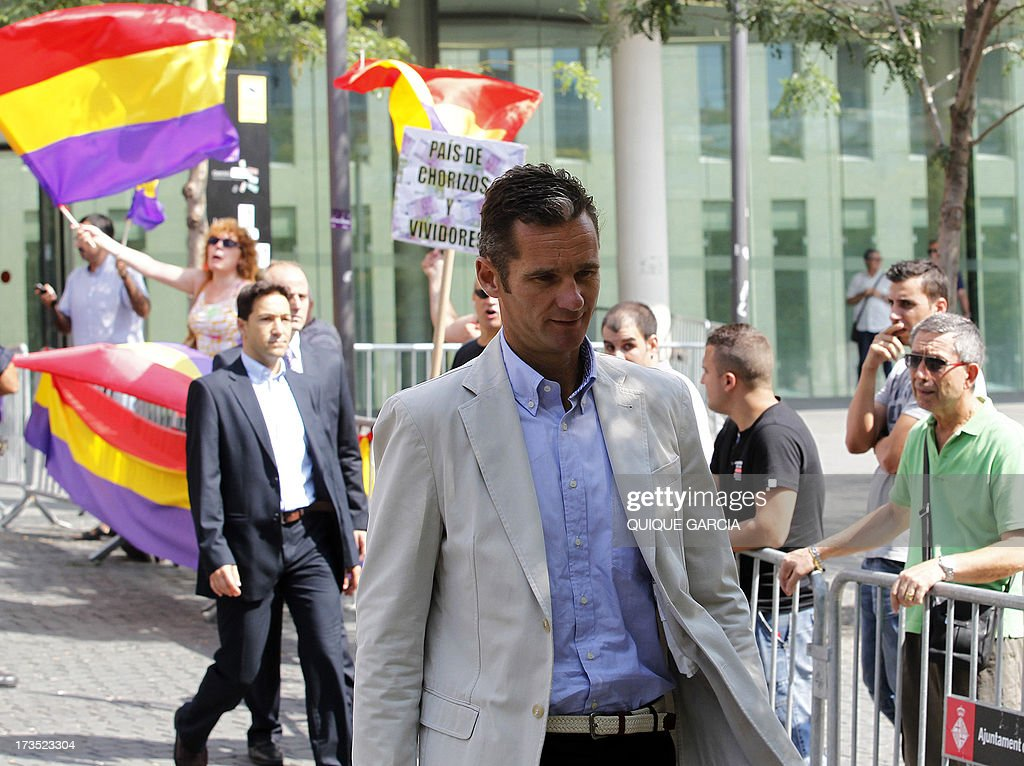 Protesters wave flags of the Second Spanish Republic as Spanish King's son-in-law Inaki Urdangarin leaves the courthouse in Barcelona on July 16, 2013. The Duke of Palma appeared in front of a judge today to testify as witness over his complaint for alleged breach of privacy rights following the publication of personal emails in different media. Inaki Urdangarin and former partner Diego Torres are suspected of syphoning off millions of euros paid by regional governments to the Noos Institute, a charitable organisation which Urdangarin chaired from 2004 to 2006.