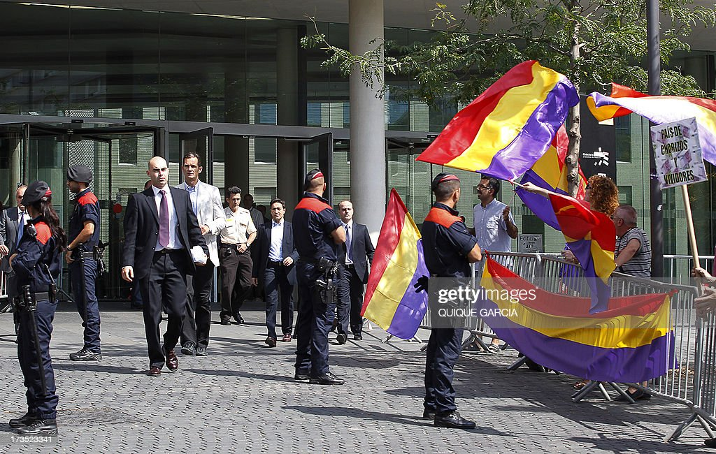 Protesters wave flags of the Second Spanish Republic as Spanish King's son-in-law Inaki Urdangarin (4th L) leaves the courthouse in Barcelona on July 16, 2013. The Duke of Palma appeared in front of a judge today to testify as witness over his complaint for alleged breach of privacy rights following the publication of personal emails in different media. Inaki Urdangarin and former partner Diego Torres are suspected of syphoning off millions of euros paid by regional governments to the Noos Institute, a charitable organisation which Urdangarin chaired from 2004 to 2006.