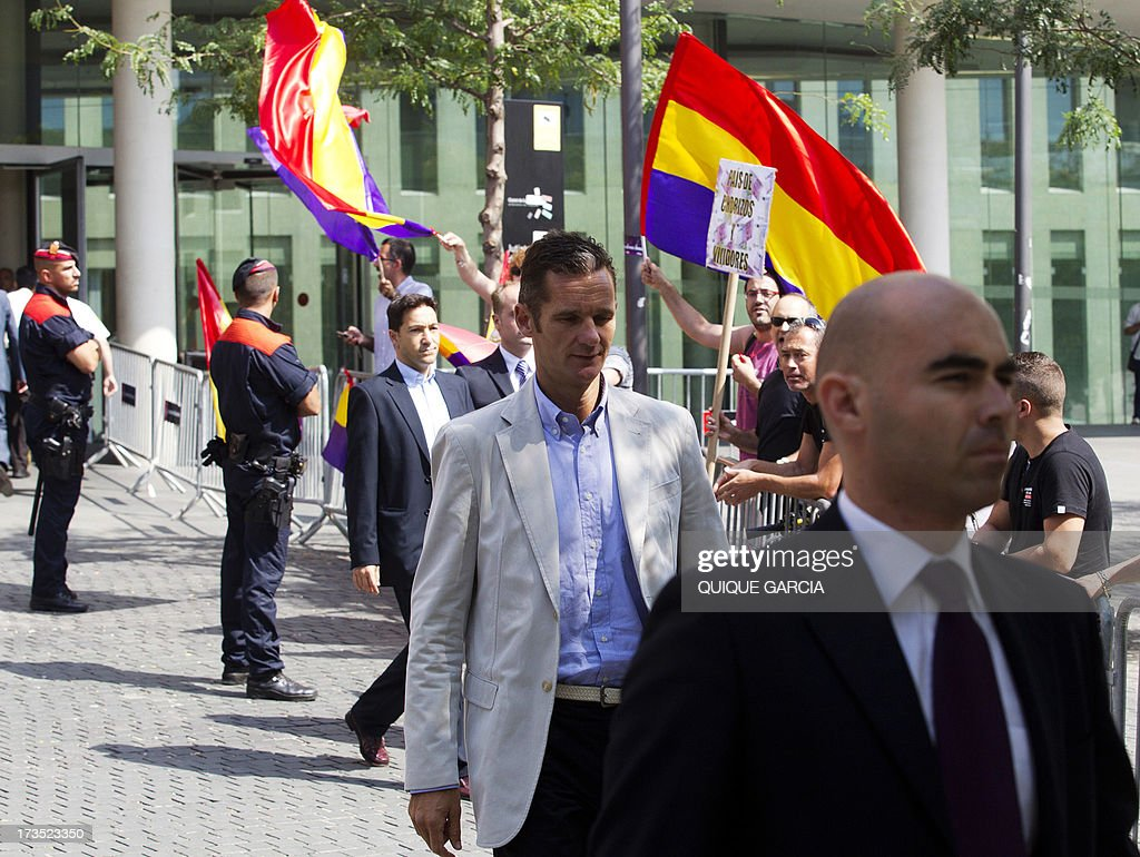 Protesters wave flags of the Second Spanish Republic as Spanish King's son-in-law Inaki Urdangarin (C) leaves the courthouse in Barcelona on July 16, 2013. The Duke of Palma appeared in front of a judge today to testify as witness over his complaint for alleged breach of privacy rights following the publication of personal emails in different media. Inaki Urdangarin and former partner Diego Torres are suspected of syphoning off millions of euros paid by regional governments to the Noos Institute, a charitable organisation which Urdangarin chaired from 2004 to 2006. AFP PHOTO / QUIQUE GARCIA