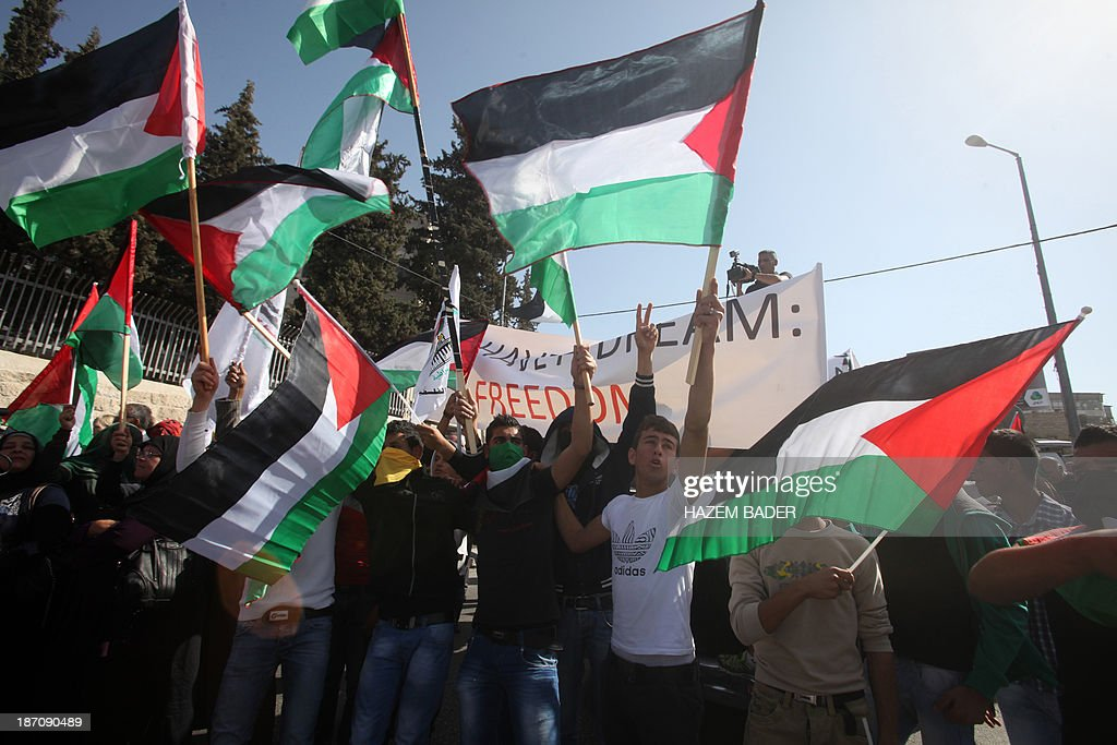 Protesters wave Palestinian flags during a demonstration to protest against US Secretary of State's visit on November 6, 2013 in Bethlehem. Just before Kerry's arrival on November 5, a meeting between the negotiators in Jerusalem broke down over recent settlement moves, with Israel advancing plans for some 3,700 new settler homes in the past week alone.