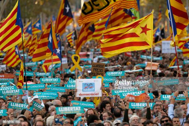 TOPSHOT Protesters wave proindependence Catalan Estelada flags along with signs calling for the release of two separatist leaders during a...