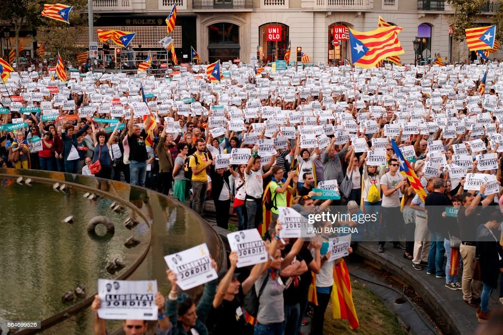 TOPSHOT - Protesters wave pro-independence Catalan Estelada flags along with signs calling for the release of two separatist leaders during a demonstration in Barcelona on October 21, 2017 in support of Jordi Sanchez and Jordi Cuixart, who have been detained pending an investigation into sedition charges. Spain announced that it will move to dismiss Catalonia's separatist government and call fresh elections in the semi-autonomous region in a bid to stop its leaders from declaring independence. / AFP PHOTO / Pau BARRENA