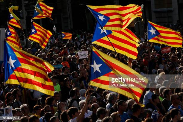 TOPSHOT Protesters wave proindependence Catalan Estelada flags during a demonstration in Barcelona on October 21 2017 in support of two leaders of...