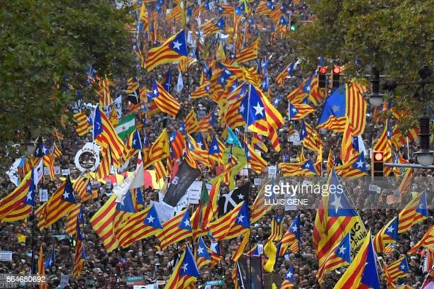 TOPSHOT Protesters wave proindependence Catalan Estelada flags during a demonstration in Barcelona on October 21 2017 in support of separatist...