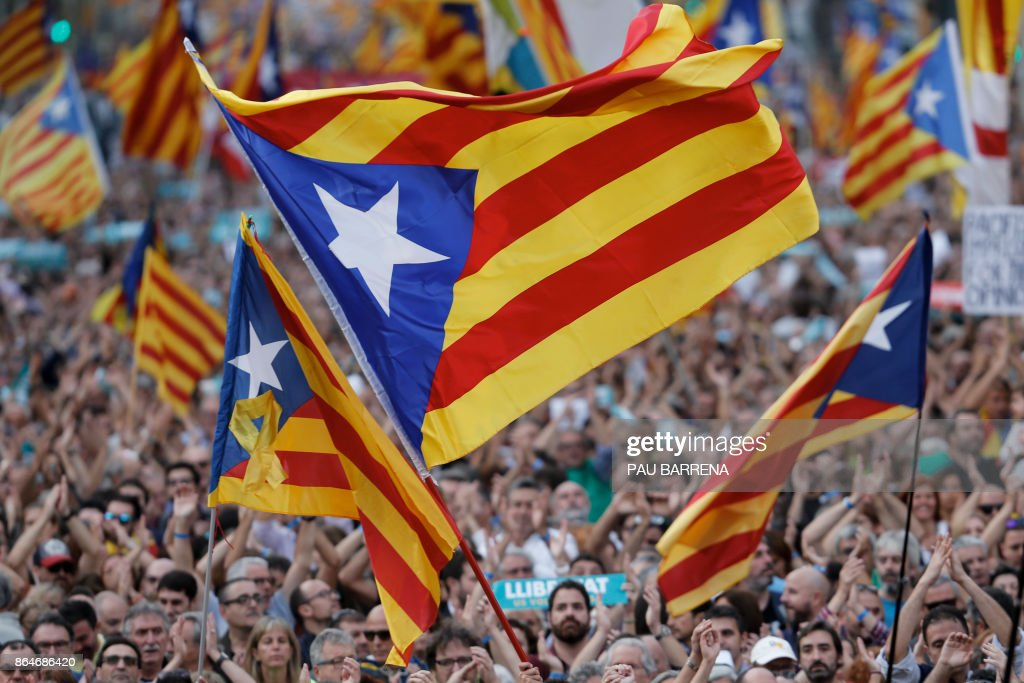 TOPSHOT - Protesters wave pro-independence Catalan Estelada flags during a demonstration in Barcelona on October 21, 2017 in support of two separatist leaders Jordi Sanchez and Jordi Cuixart, who have been detained pending an investigation into sedition charges. Spain announced that it will move to dismiss Catalonia's separatist government and call fresh elections in the semi-autonomous region in a bid to stop its leaders from declaring independence. /