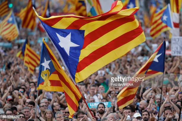 TOPSHOT Protesters wave proindependence Catalan Estelada flags during a demonstration in Barcelona on October 21 2017 in support of two separatist...