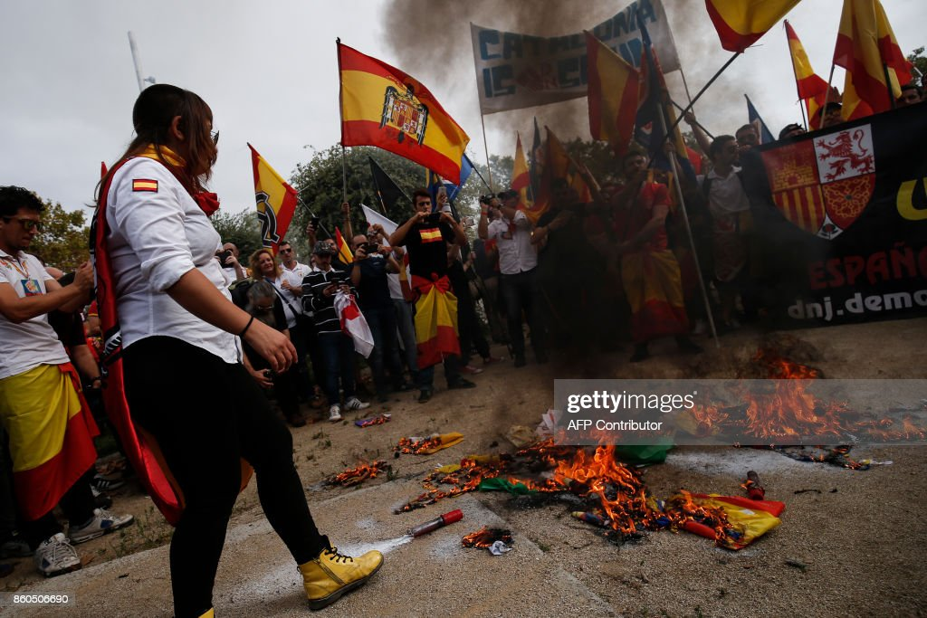 Protesters wave Spanish pre-constitutional flags and burn 'Esteladas' Catalan pro-independence flags during an ultra-right wing anti-separatist demonstration for the unity of Spain called by 'Falange Espanola' during the Spanish National Day (Dia de la Hispanidad) in Barcelona on October 12, 2017. Spain marks its national day today with a show of unity in the face of Catalan independence efforts, a day after the central government gave the region's separatist leader a deadline to abandon his secession bid. The country is suffering its worst political crisis in a generation after separatists in the wealthy northeastern region voted in a banned referendum on October 1 to split from Spain BARRENA