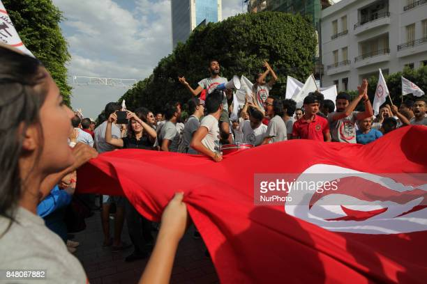 Protesters wave Tunisian flag and shout slogans during a march held under the slogan firmness against the mafia regime by the movement quotI don't...