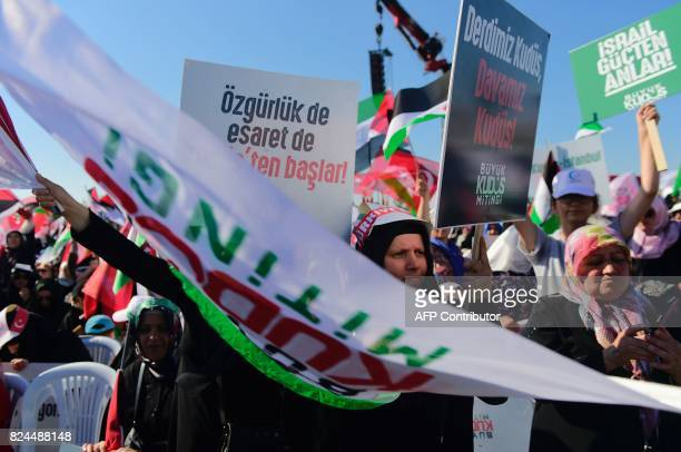 Protesters wave Turkish and Palestinian flags as they hold a placard reading 'Israel understands power' during a demonstration in Istanbul on July 30...