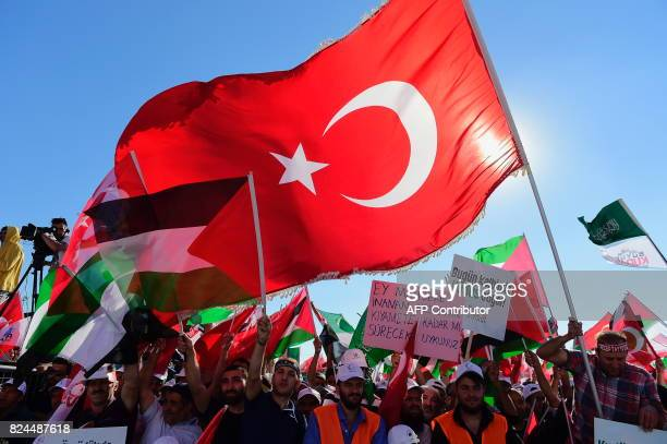 Protesters wave Turkish and Palestinian flags as they hold placards reading 'Our hearts beat for Jarusalem' during a demostration in Istanbul on July...